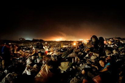 10. Two boys are sleeping in city's toxic garbage dump. The dump provides food and shelter for the many homeless. Photographer: Mads Nissen / GraziaNeri