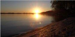 Odpocznij na jeziorem zachodzącego słońca.