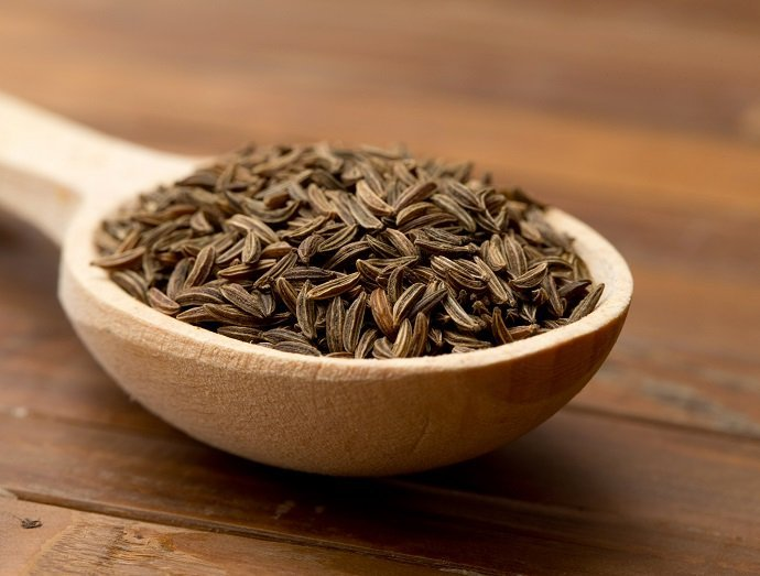 cumin seeds in a wooden spoon