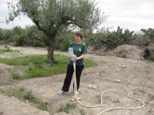 Une personne tient un des piquets du niveau et reste au même endroit autant que la longueur du tuyau le permet.