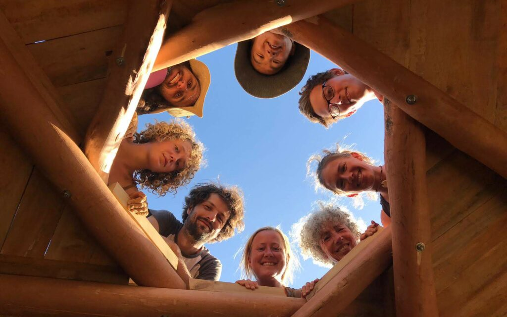 a group of graduated natural builders on a reciprocal roof