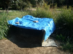 A tarp covers the grey water grease trap