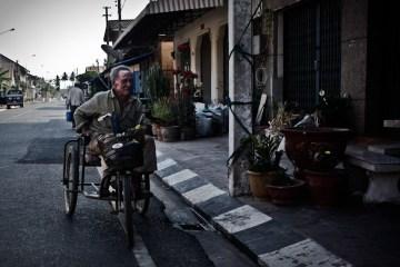 """Mężczyzna na trój kołowym """"rowerze"""""""