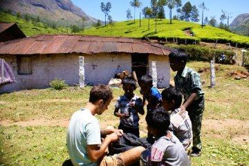 Hinduskie dzieciaki wyciagają ręce po długopisy