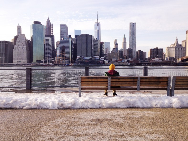 Man sitting on a bench facing a city.