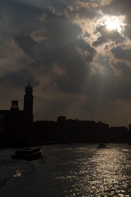 Un impresionante sol se cuela entre las nubes durante el atardecer en Murano, Italia