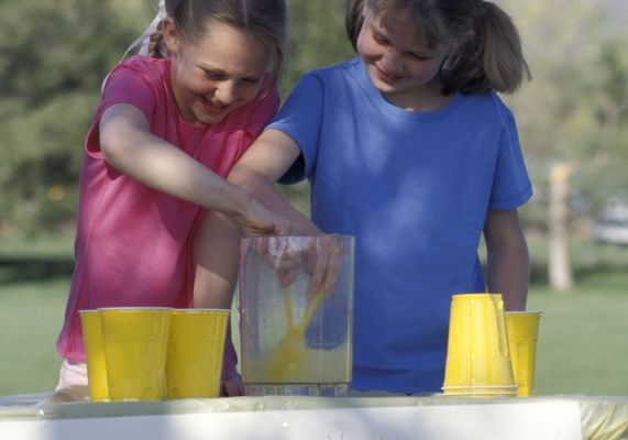 Two girls at their lemonade stand in a Perry Homes lawn.