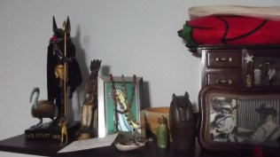 Left side of the ancestor shrine. Anubis, Djehuty, and Aset as Lady of the West sit at the end. Then there's my Marian shrine, along with two canopic jars and a libation bowl. The jewellery case and the folded up Welsh flag on top of it belonged to my maternal grandparents, who are in the photo in front of it.