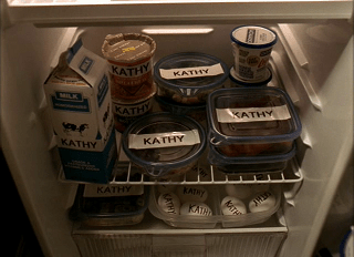 A refrigerator full of food with enormous labels that say Kathy