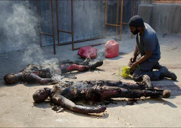 """A man with kneels over two burned corpses in The Walking Dead 4.03 """"Isolation."""""""