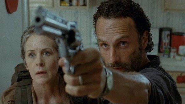 Rick pulls a gun, Carol looks on.