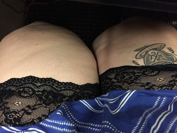 A picture of pale, fat thighs wearing black lace Bandalettes under a blue skirt.