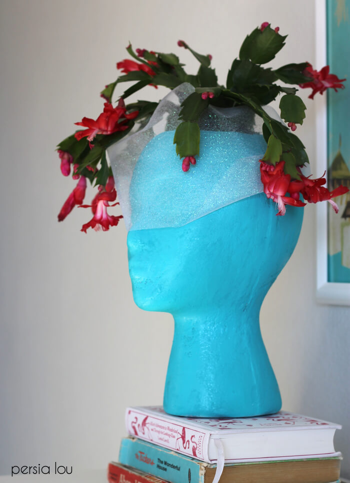 finished blue foam head planter with pink christmas cactus on bookshelf