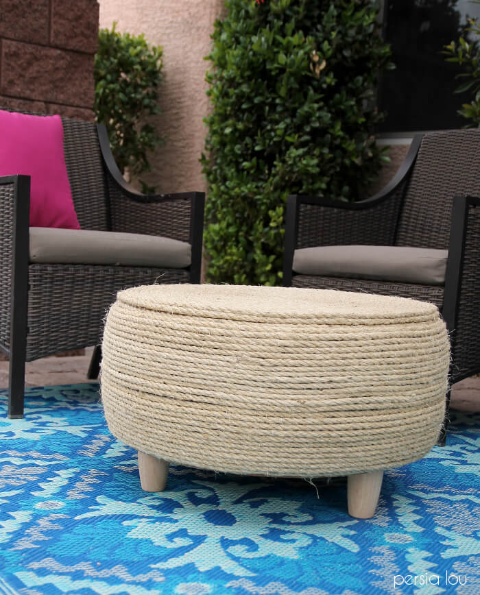 finished diy tire coffee table wrapped in light sisal rope and sitting on blue patio rug