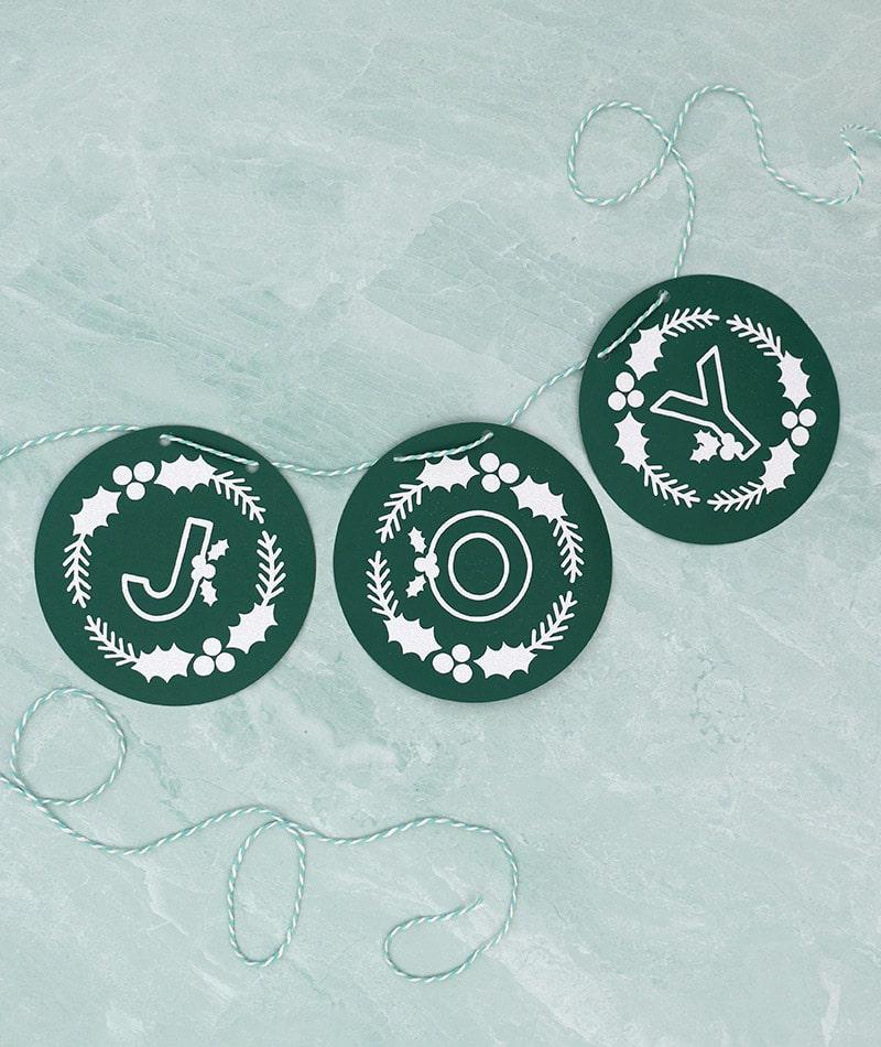 diy paper joy banner made using dark green cardstock, white glitter heat transfer vinyl, and free winter monogram cut files