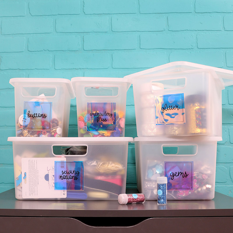 """Five clear plastic bins filled with craft supplies sit on a gray table in front of a turquoise brick wall. The bins have iridescent labels on them that read """"buttons,"""" """"embroidery floss,"""" """"sewing notions,"""" """"glitter,"""" and """"gems."""" Two small jars of glitter sit on the table in front of the bins."""