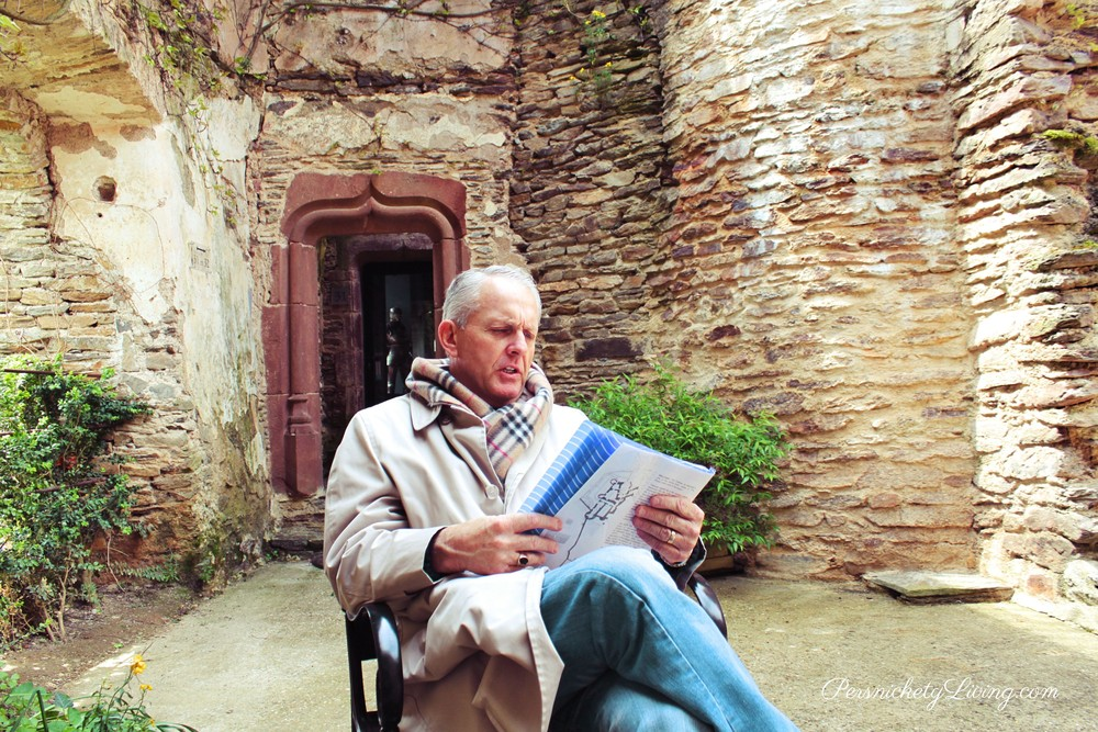 My husband reading about the castle in French town Belcastel