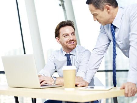 Führungskraft im Gespräch mit Mitarbeiter am Arbeitsplatz