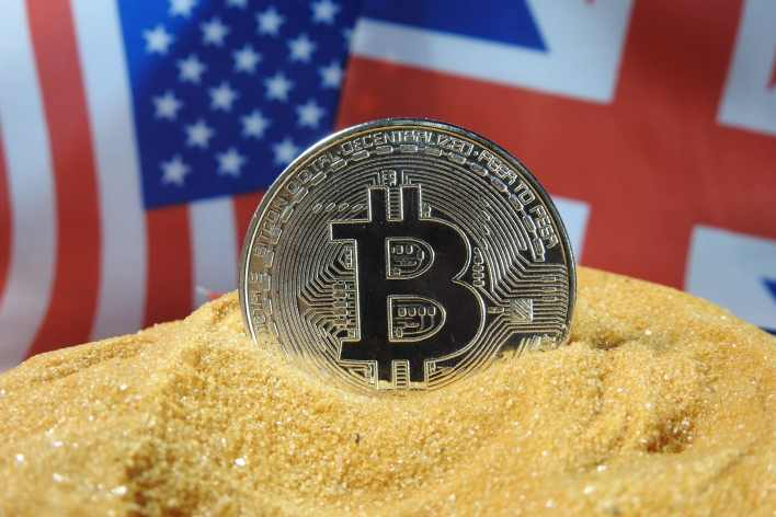 A silver Bitcoin cryptocurrency with United States and United Kingdom flag in the background