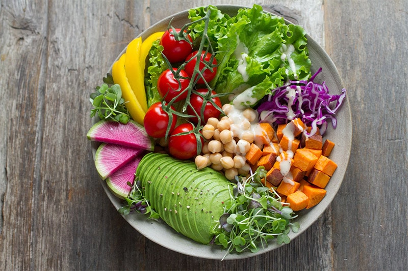 Vegan salad with lettuce, cherry tomatoes, cabbage, pumpkin, chickpeas and avocado