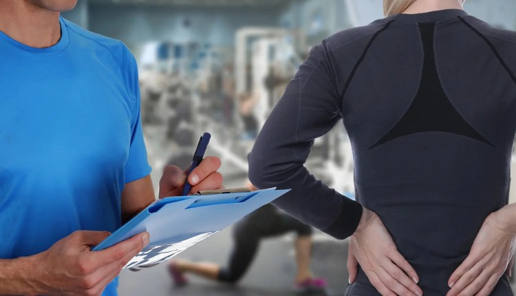 chiropractor takes notes from woman with low back pain