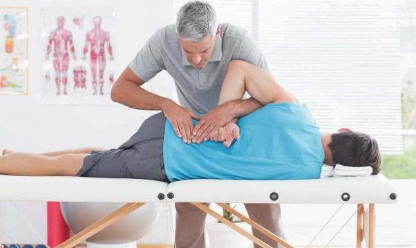Imagen de un quiropráctico que usa ajustes espinales para tratar a un paciente por dolor lumbar.