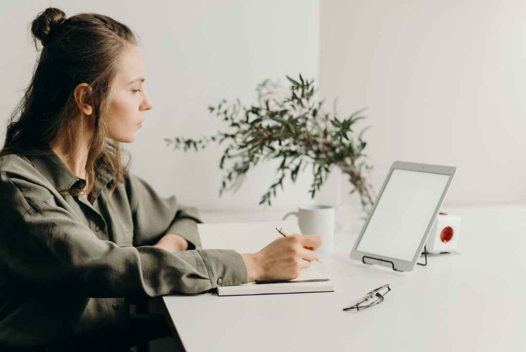 woman in gray coat using white laptop computer