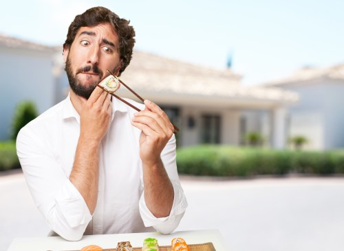 A man looks fearfully at his high glycemic index sushi.