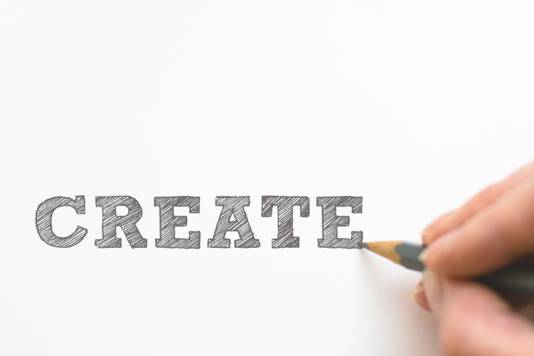 Picture of somebody writing the word 'create' with a pencel