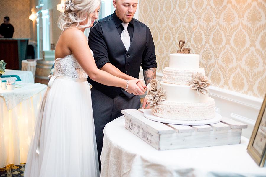 katye and frank cut their wedding cake at tomasello winery