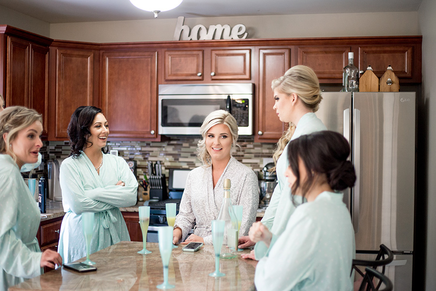 bride and bridesmaids getting ready in aqua matching robes