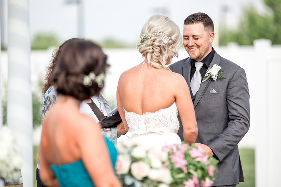 groom smiles at his bride during the wedding ceremony at tomasello winery