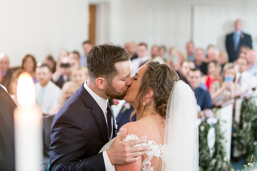 bride and groom share first kiss at married couple