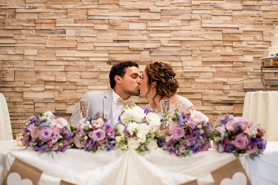 bride and groom kiss at their sweetheart table