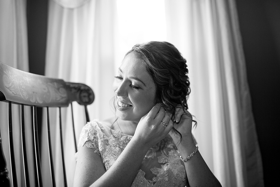 bride putting on her earrings at her moms house
