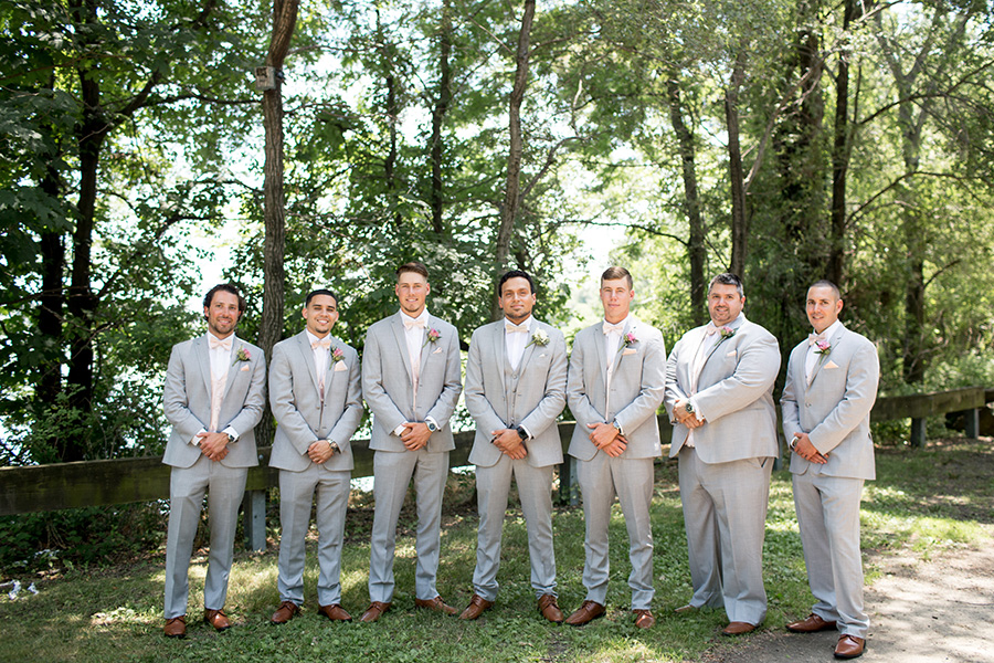 groom with his groomsmen all wearing gray tuxes