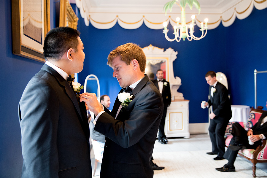 groomsmen straighten their ties before wedding at congress hall