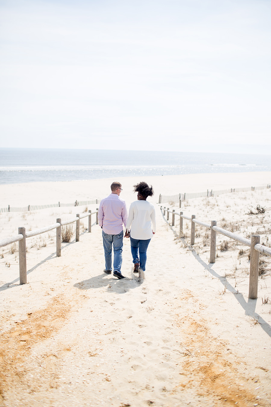 engaged couple walks on the beach in LBI