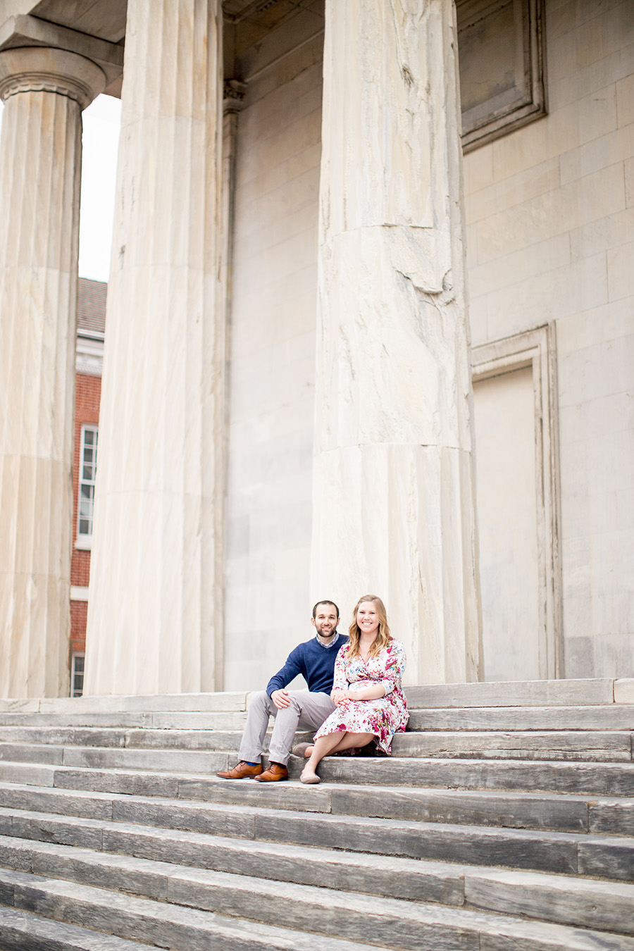 engaged pair sits on steps together