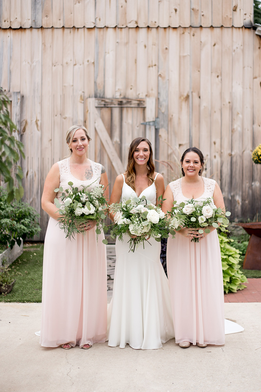 bride and bridesmaids pose with the neutral background in front of the barn