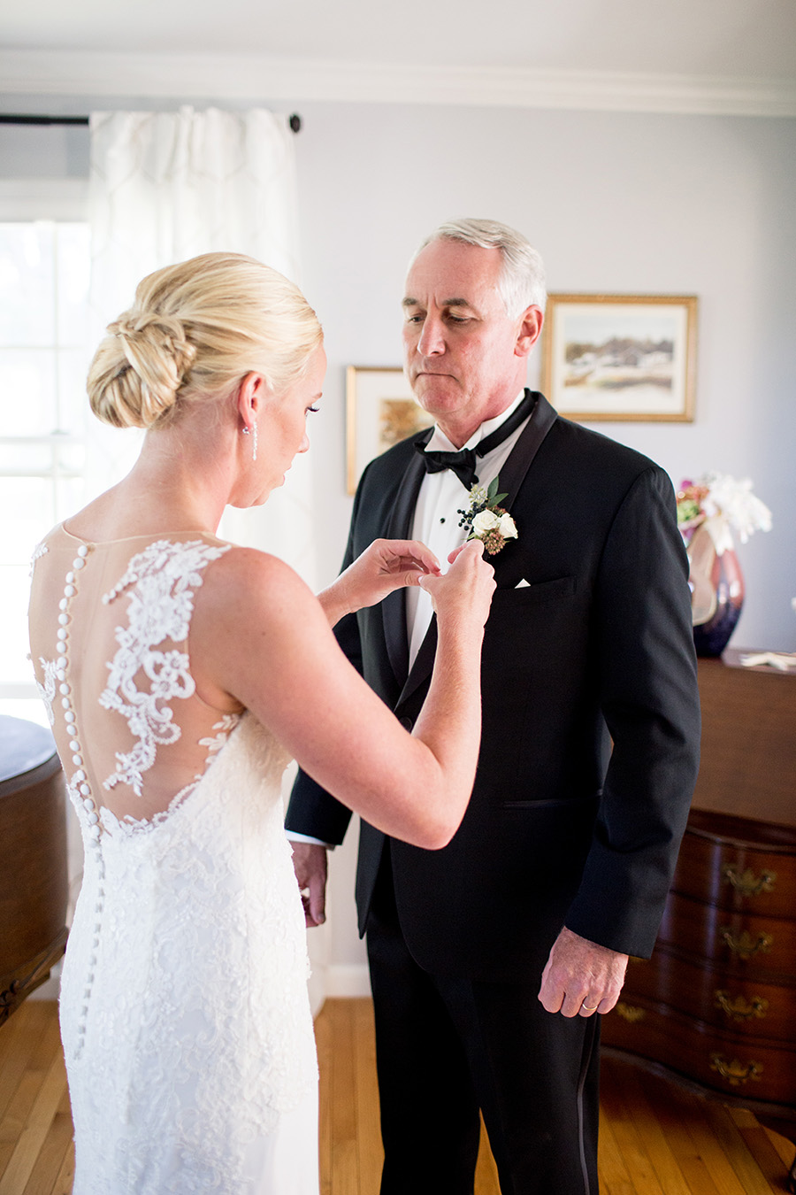 bride pinning boutonniere on her dad