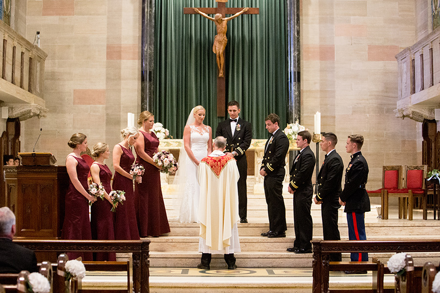 bridesmaids and groomsmen stand with the couple at the altar