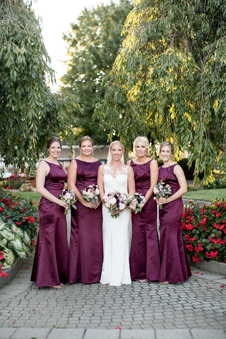 bridesmaids wear floor-length plum gowns