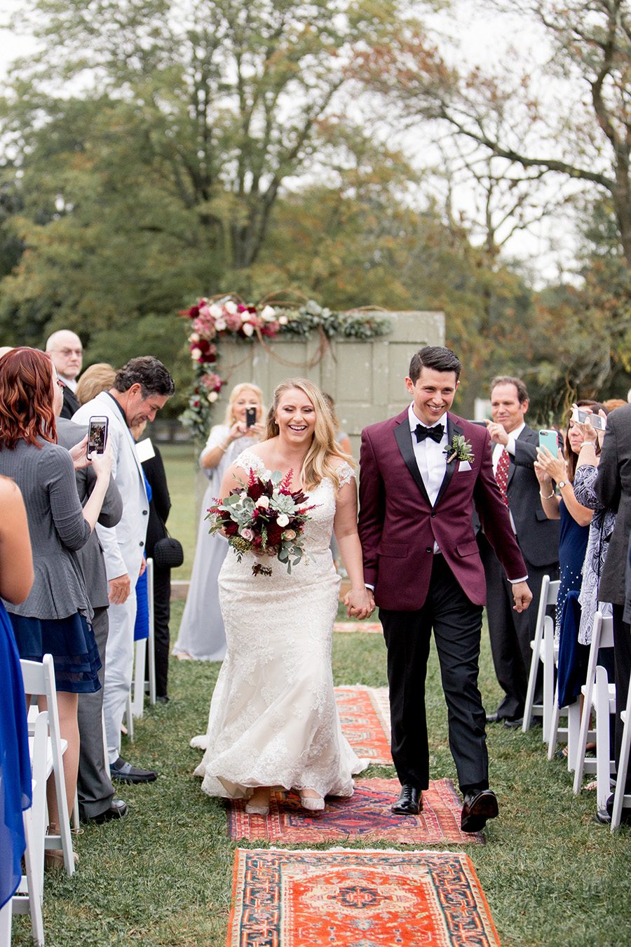 newly married couple walk down the aisle together