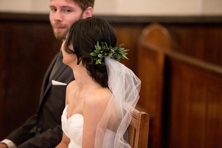 bride wears a floral hair piece