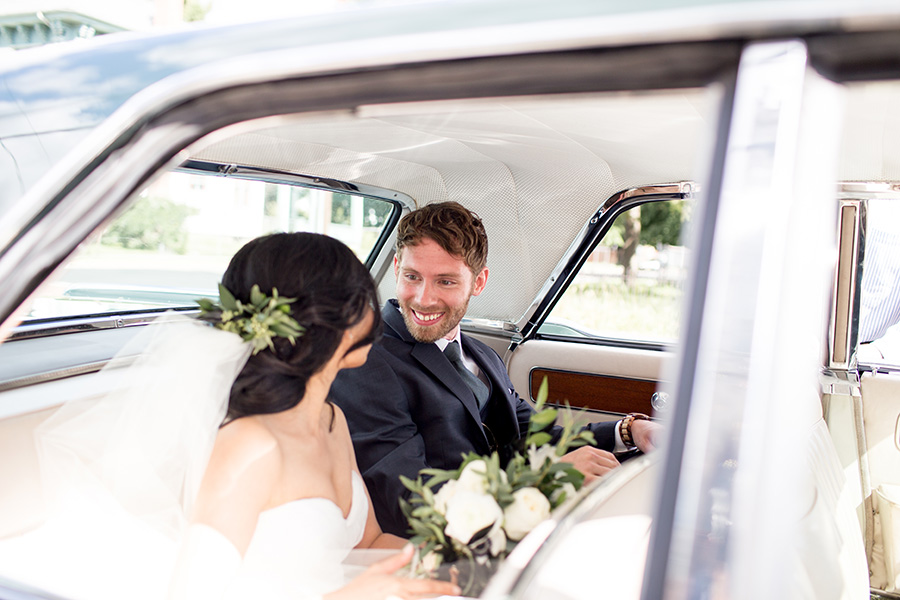 the happy couple in the back of their getaway car