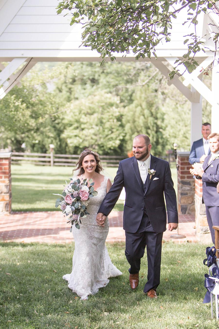 husband and wife walking back down the aisle