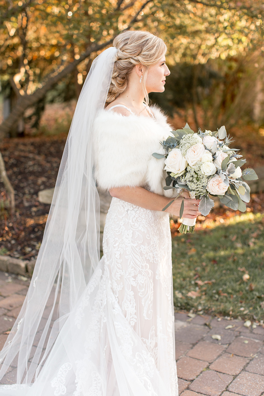 bride with winter wedding shrug and lace gown