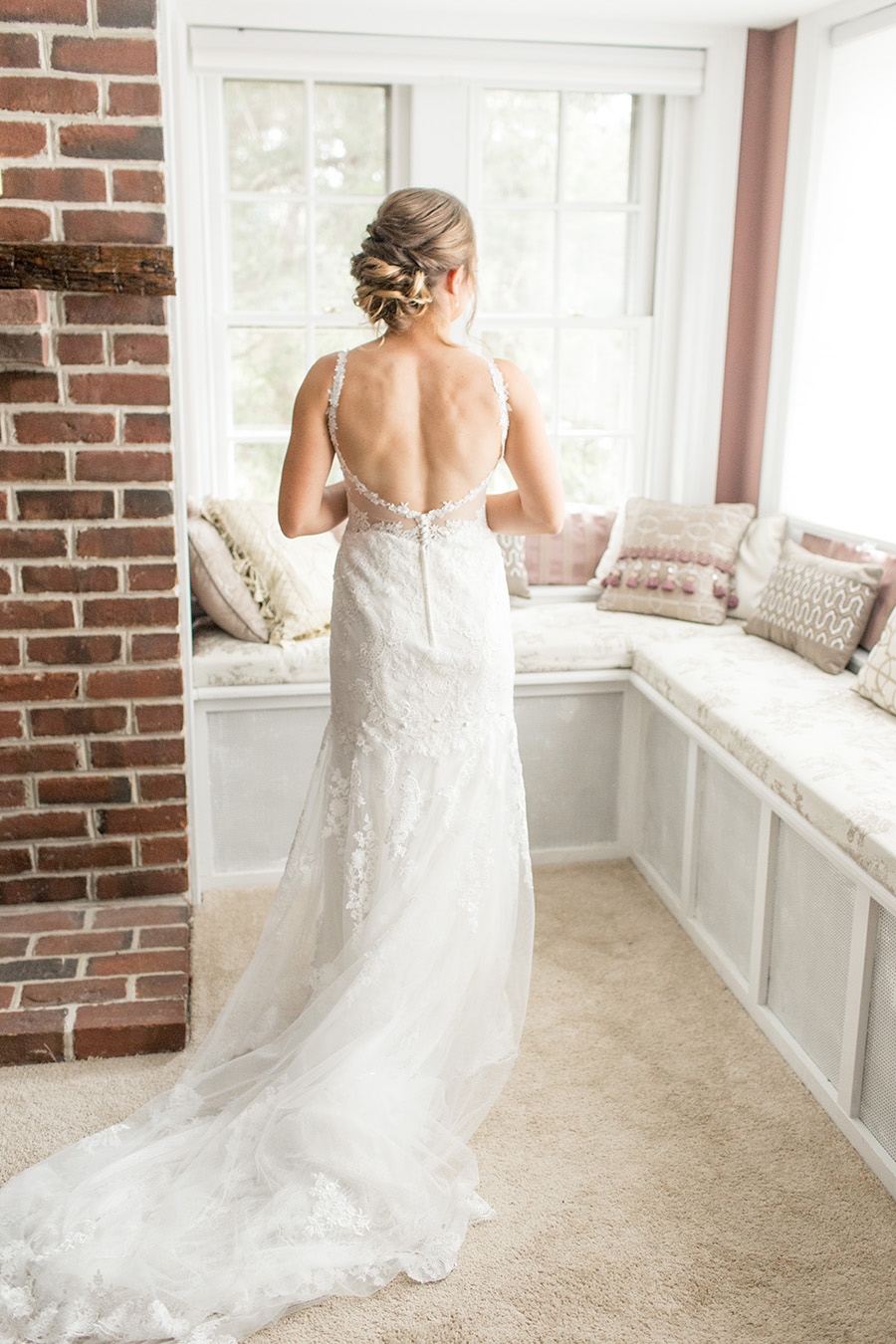 bride looking out the window in an open back lace wedding dress