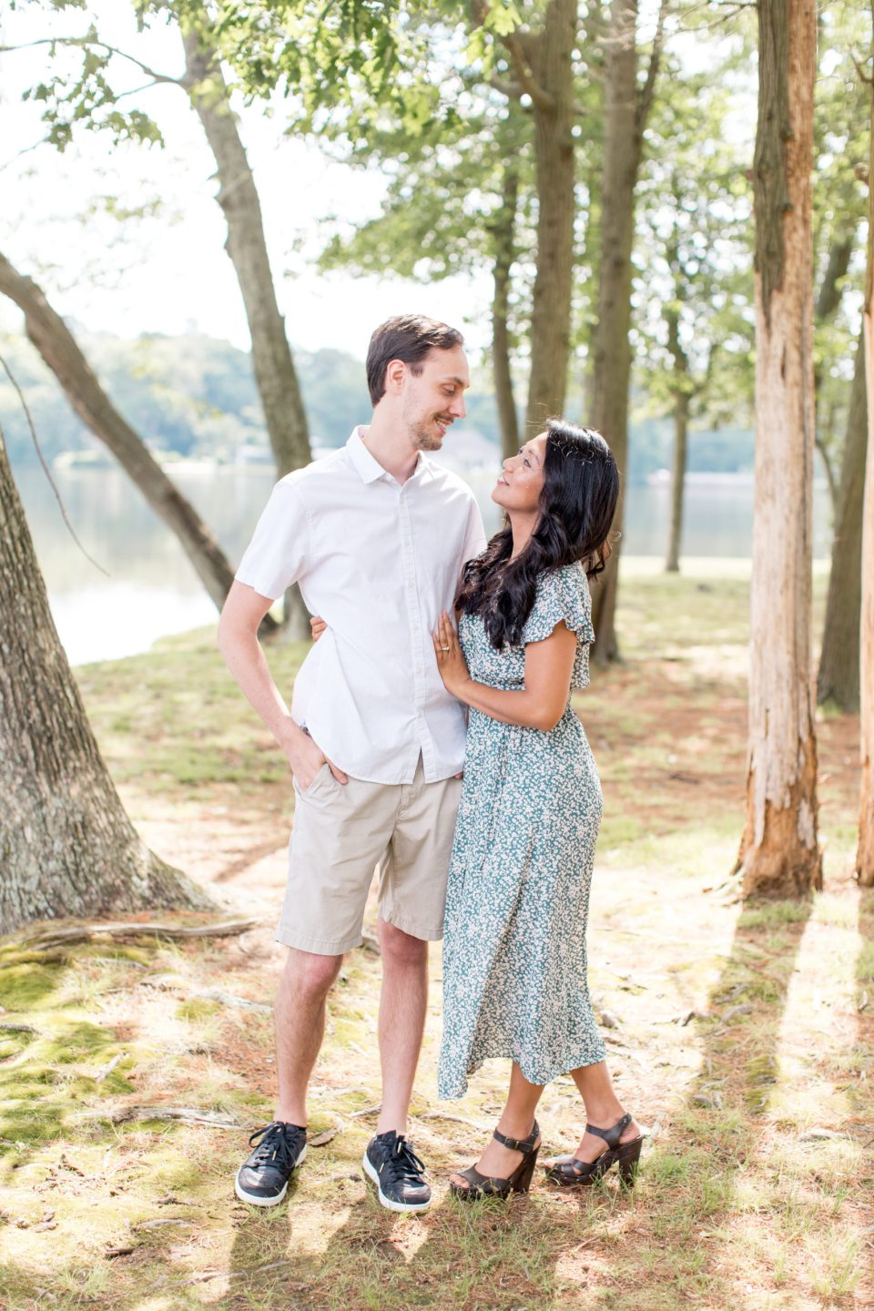 couple poses for engagement portraits at piney point on sunset lake